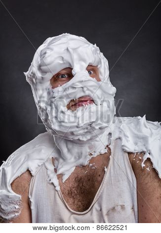 Bizarre man with face completely in shaving foam thinks over grey