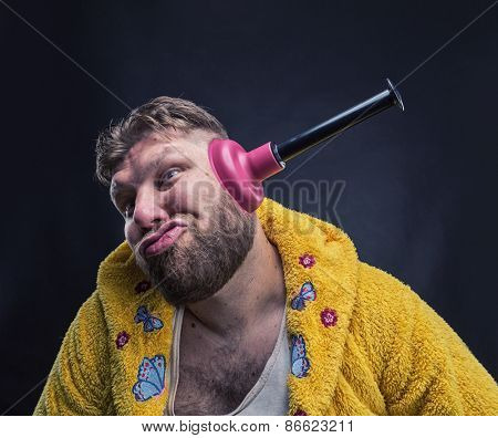 Strange man in a terry bathrobe with a plunger in his ear