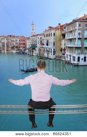 Businessman sitting on light metal girder beam with view of Venice, in background