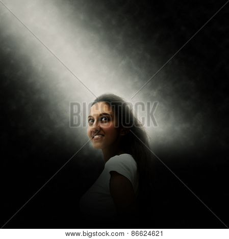 Smiling pretty young Indian woman lit by a shaft of light shining down through the darkness in square format