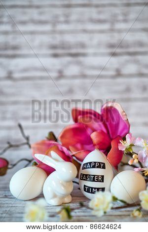 Small White Rabbit Figurine with Easter Eggs Surrounded by Pink Blossoms on Rustic Wooden Background