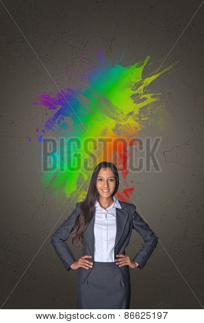 Artistic colorful portrait of a stylish confident young Asian businesswoman standing with her hands on her hips surrounded by a vivid splash of color in the colors of the rainbow