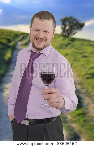 Businessman holding glass of wine with sunset landscape in background