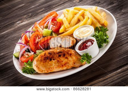 Fried chicken fillet, chips and vegetable salad