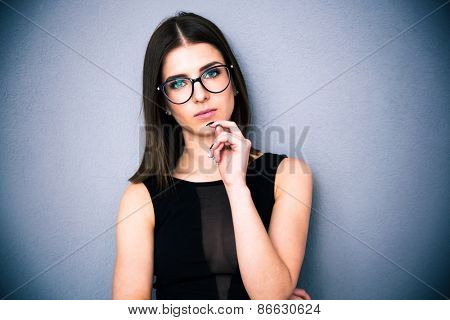 Portrait of a pretty thoughtful woman in glasses looking at camera. Standing over gray background