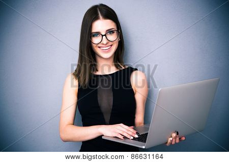 Cheerful young woman with laptop standing over gray background. Wearing in fashion black dress and glasses. Looking at camera