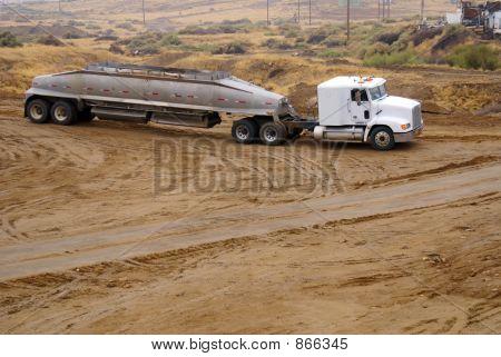 Spreader distributes soil over construction job site