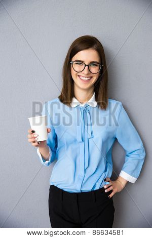Portrait of a smiling businesswoman holding cup with coffee over gray background. Wearing in blue shirt and glasses. Looking at camera