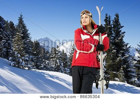 Pretty young women, holding her skies in front of an alpine mountain range with snow covered trees and fresh powder snow,
