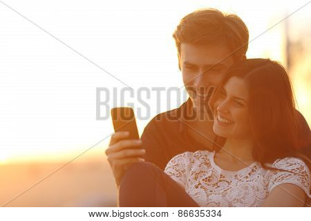 Back Light Of A Couple Sharing A Smart Phone