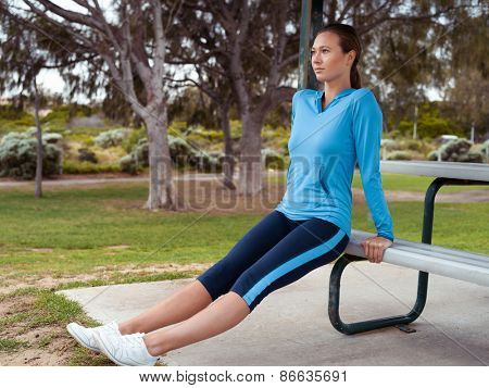 Sporty young woman stretching in the park