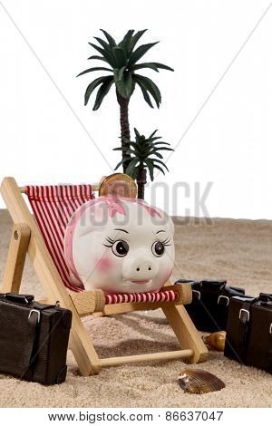 a piggy bank is in a deck chair. symbolic photo for airline travel and expenses on vacation
