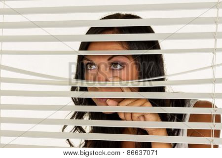 a young woman watching something through the blinds of her window