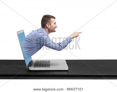 smiley businessman got out of the laptop and pointing at empty copyspace against white background