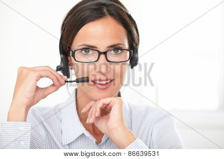 Smiling Hispanic Secretary Talking On Headphones