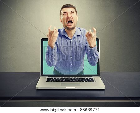 emotional screaming man got out of the laptop against dark background