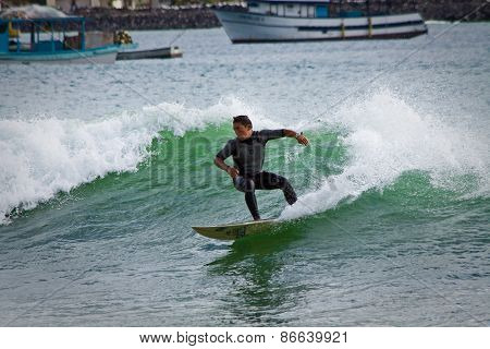 Unidentified man surfing in Mann beach, San Cristobal Island, Galapagos