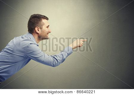 smiley handsome businessman in shirt pointing at something against dark background