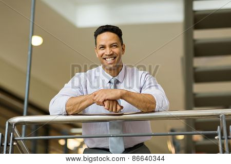 cheerful businessman standing by stairway