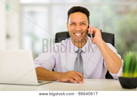 portrait of happy middle aged corporate worker talking on cell phone