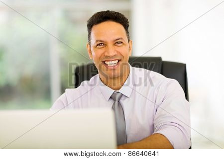 portrait of handsome middle aged businessman in front of laptop