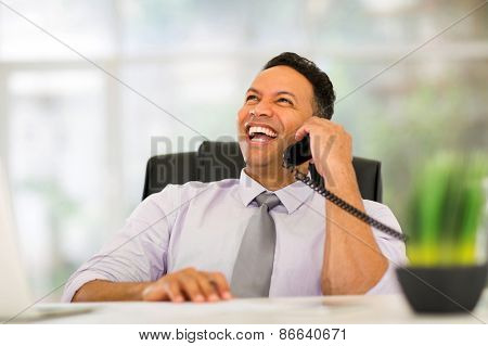 happy middle aged corporate worker talking on landline phone in office