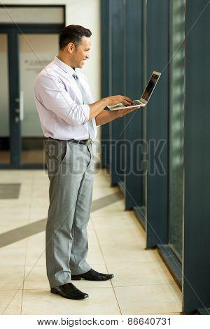 full length portrait of caucasian businessman using laptop computer