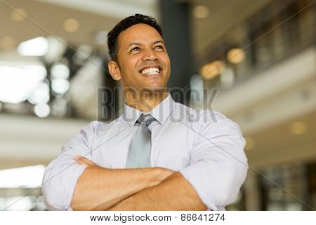 cheerful mature businessman looking up in office