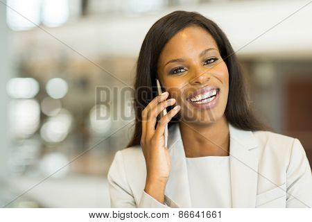 cheerful afro american business woman talking on cell phone in office