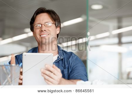 Portrait of a handsome young man working with a tablet in an office