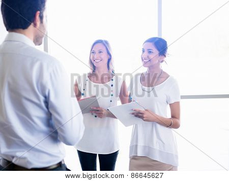 Two young female collegues meeting a new coworker