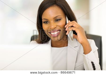 cheerful young afro american business woman talking on cell phone