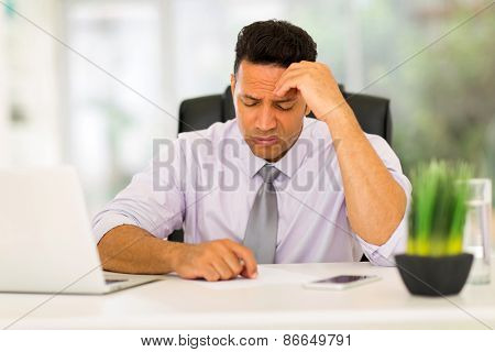 stressed businessman having headache at work