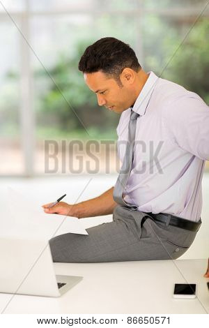 busy middle aged businessman reading report in office