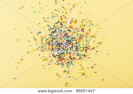 Colorful Round Sprinkles Spilled On Yellow Background, Isolated