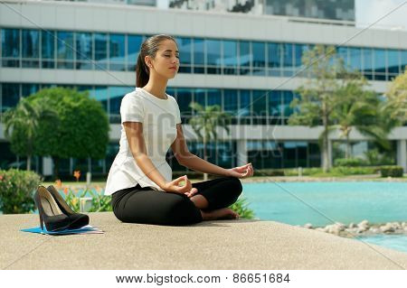 Business Woman Doing Yoga Lotus Position Outside Office Building