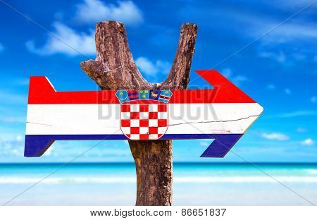 Croatia wooden sign with a beach on background