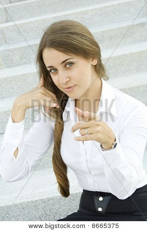 Businesswoman gesturing call me pointing to viewer