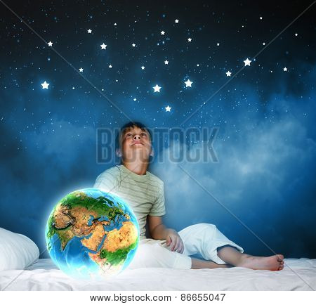 Cute boy sitting in bed and looking at Earth planet. Elements of this image are furnished by NASA