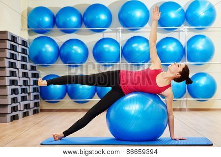 female instructor balancing on fitness ball during pilates exercises in sport club