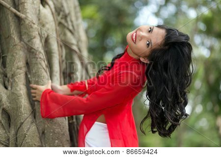 Charming Vietnamese woman bending over a large fig tree in a park, Vietnam