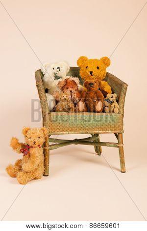 Group stuffed vintage bears sitting in old vintage chair