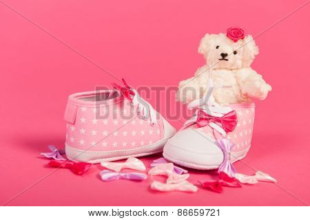 White hand made teddy bears and pink baby shoes