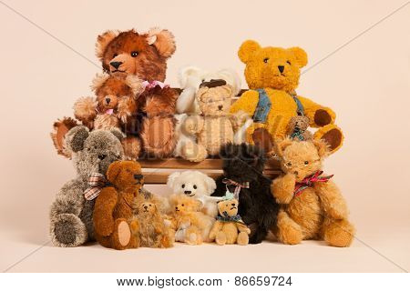 Stuffed vintage bears sitting on bench for family portrait at beige background