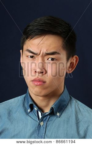 Serious young Asian man looking at camera