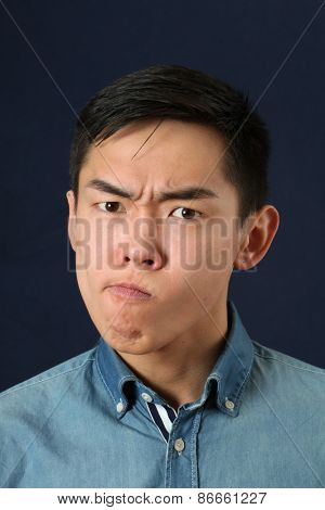 Displeased young Asian man making face and looking at camera