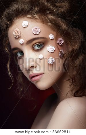 Romantic young beautiful girl with white flowers on her face and soft curls on dark background.