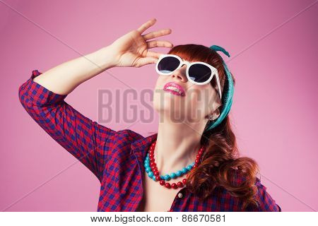 Beautiful Pin-up Girl Posing With White Sunglasses Against Pink Background