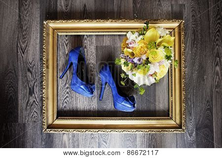 Wedding shoes and bouquet in gold frame. wedding details