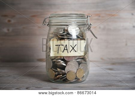 Coins in glass money jar with tax label, financial concept. Vintage wooden background with dramatic light.